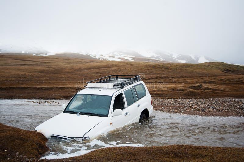Ongeval op de weg, autoneerstorting Jeep 4x4 in de stroom die van de bergrivier wordt geplakt De auto in de rivier is verdronken  royalty-vrije stock foto
