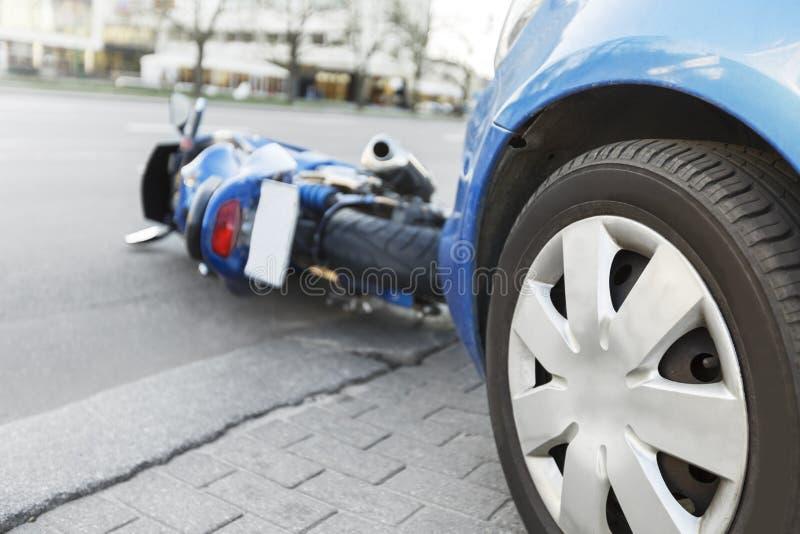 Ongevallenmotorfiets en auto's op weg stock foto's