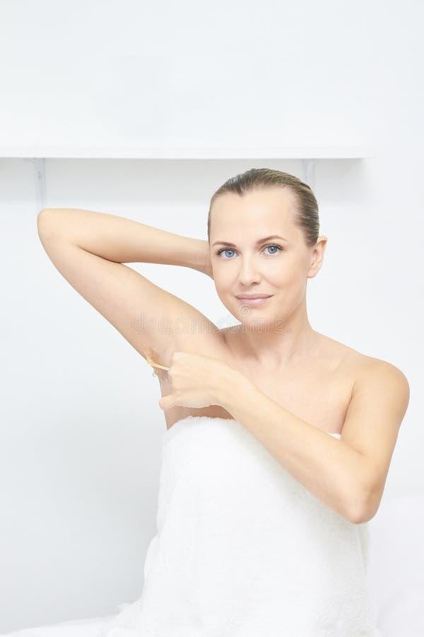 Ongewenste epilation van de haarwas Jonge Vrouw 15 de behandelingsprocedure van de de kosmetieksalon Huis het in de was zetten stock foto