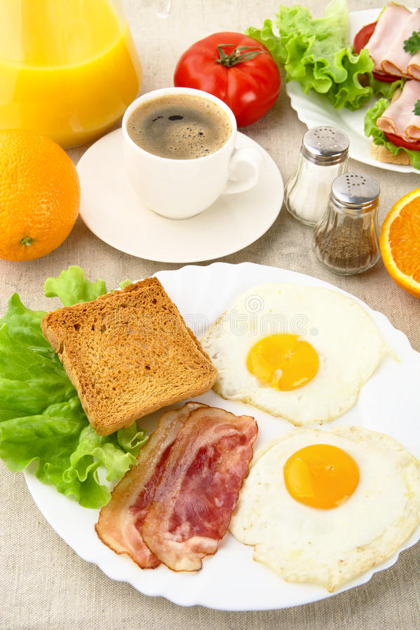 Ongezond vettig ontbijt met kop van koffie met bacon, eieren stock foto's