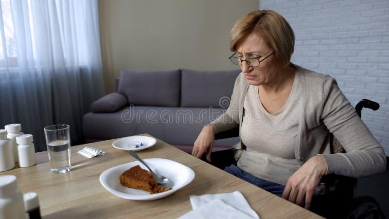 Ongezonde hogere vrouw die pijn in verpleeghuis voelen, die weigeren te eten, oude dag royalty-vrije stock afbeeldingen