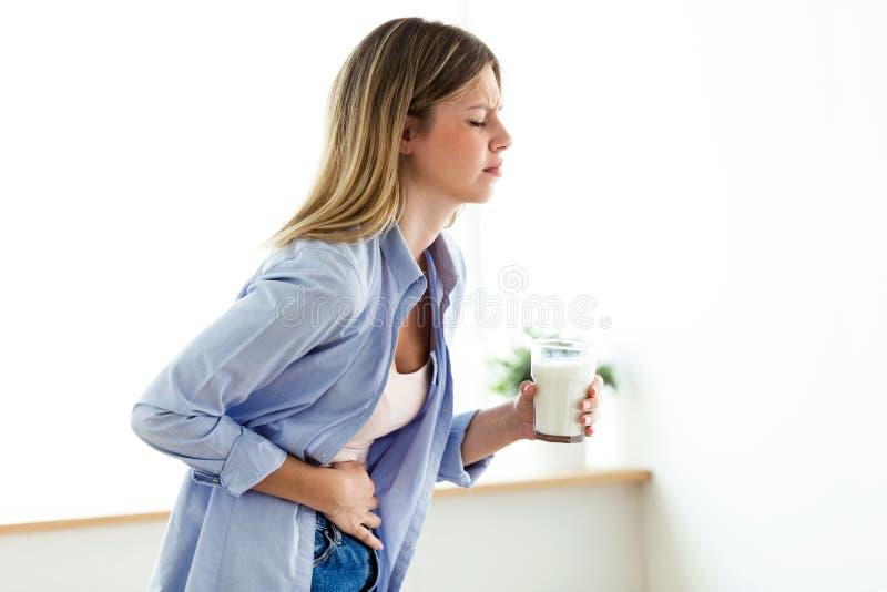 Ongezonde jonge vrouw die met maagpijn een glas met melk thuis houden stock foto