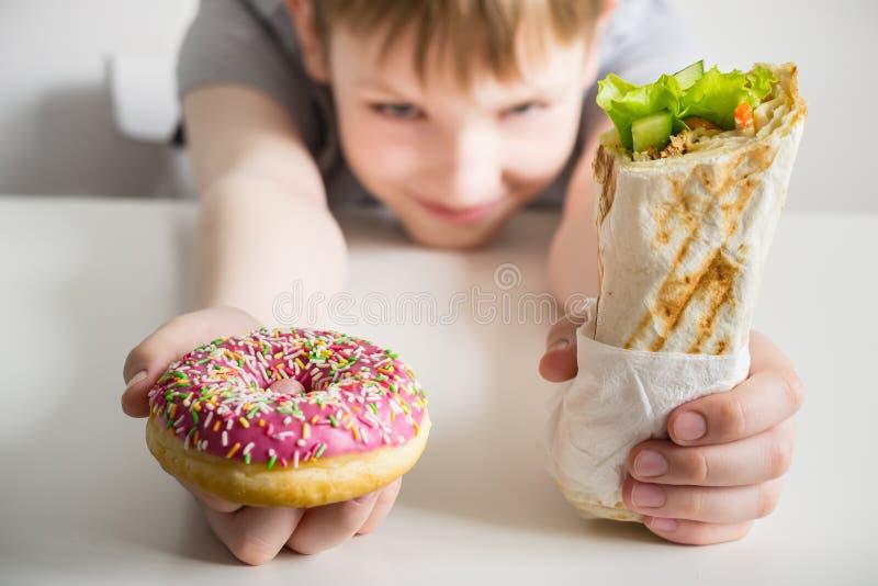 Ongezonde kost en kindconcept Tienerjongen die een doughnut in het suikerglazuur en shawarmasandwichbroodje houden stock afbeeldingen