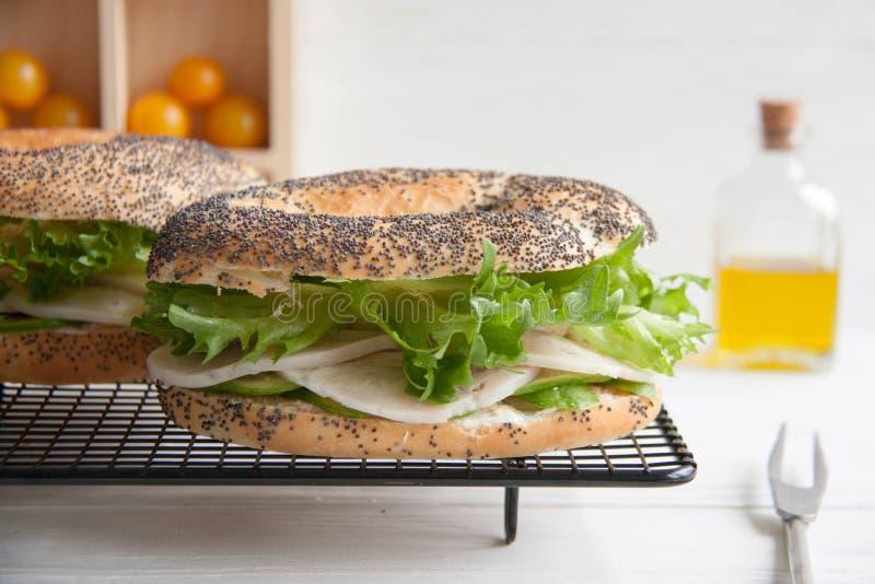 Ongezuurd broodje met kippenbroodje, groene salade en roomkaas stock afbeelding
