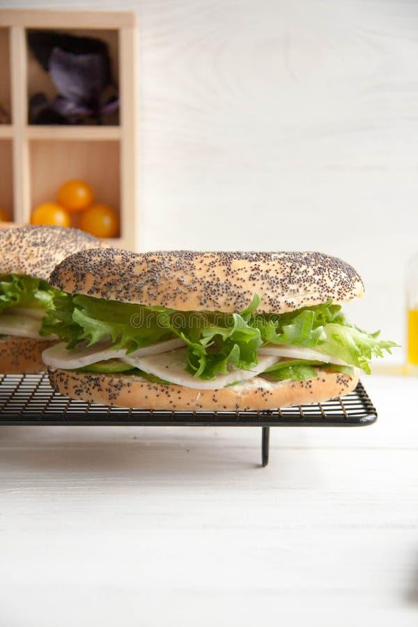 Ongezuurd broodje met kippenbroodje, groene salade en roomkaas royalty-vrije stock foto's
