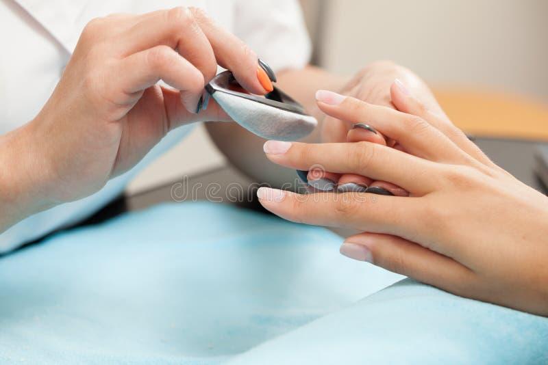 Ongle de studio — esthéticien polissant les ongles femelles images stock