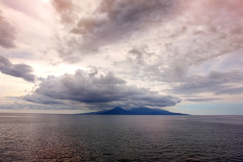 Onheilspellende zonsondergang over eiland stock fotografie