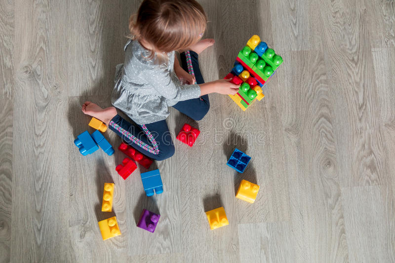 Onherkenbaar Kindmeisje die pret en bouwstijl van heldere plastic bouwblokken hebben Peuter het spelen op de vloer Het ontwikkele stock foto's