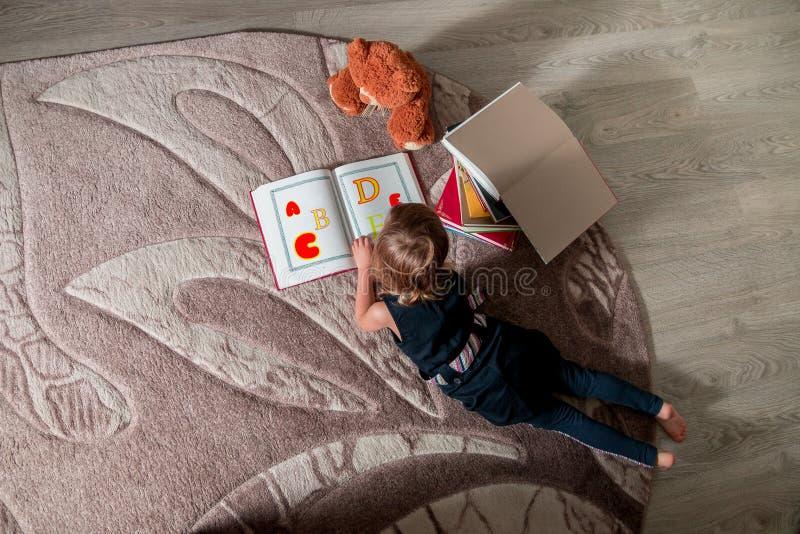 Onherkenbaar meisje in een donkerblauw boek die van de kledingslezing op de vloer dichtbij teddybeer liggen Het kind leest verhaa royalty-vrije stock afbeelding