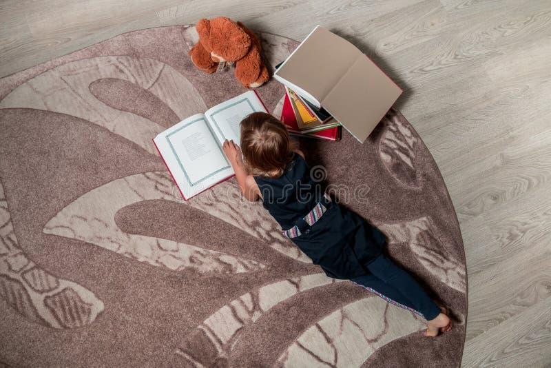 Onherkenbaar meisje in een donkerblauw boek die van de kledingslezing op de vloer dichtbij teddybeer liggen Het kind leest verhaa royalty-vrije stock foto