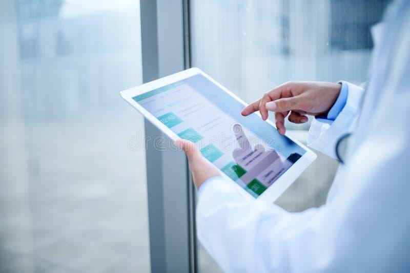 Onherkenbare arts met tablet in het ziekenhuis, werkend royalty-vrije stock foto's