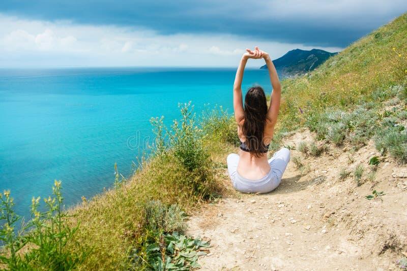 Onherkenbare atletische vrouw 25-30 die op de heuvel in bustehouder en broek zitten Het doen van yoga stock fotografie