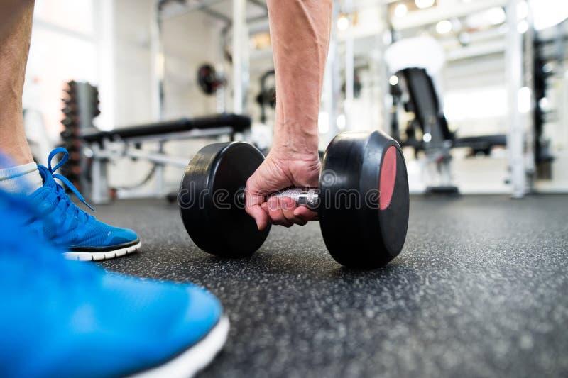 Onherkenbare hogere mens die in gymnastiek met gewichten uitwerken royalty-vrije stock afbeeldingen