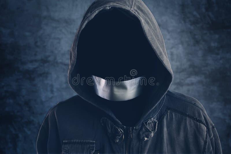 Onherkenbare hooligan met een kap met vastgebonden mondbuis royalty-vrije stock foto's