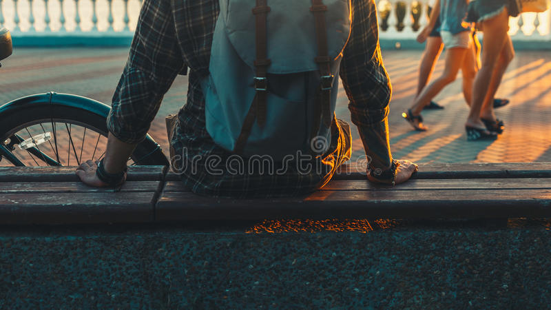 Onherkenbare Jonge Mensenzitting op Volgende aan Fiets die bij de Reizende Ontspanning van de Zonsondergangvakantie van Rustend C royalty-vrije stock fotografie