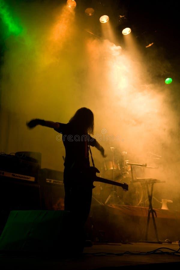 Onherkenbare musicus met gitaar op het stadium stock foto's