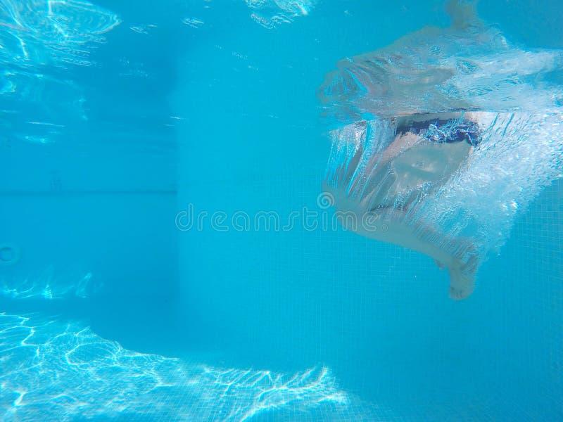Onherkenbare persoon die in water springen stock foto's