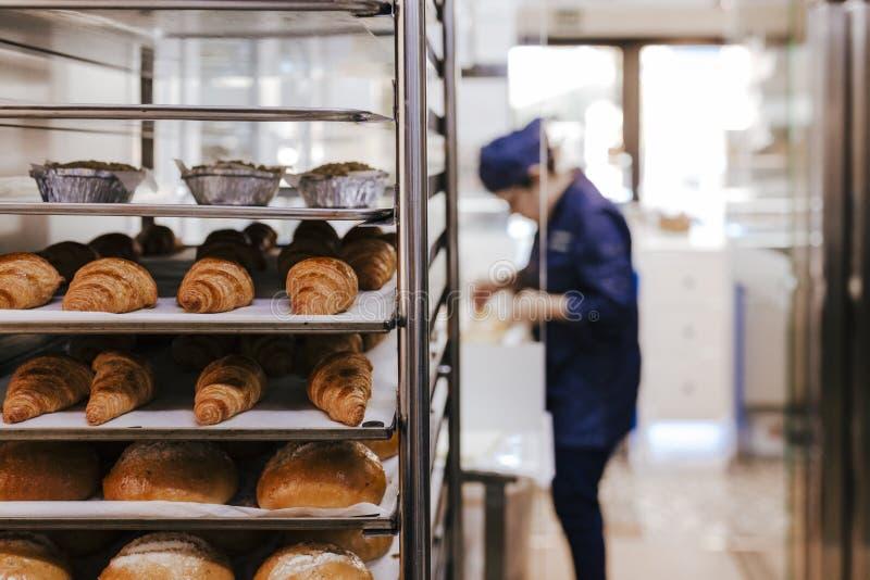 Onherkenbare vrouw bij de bakkerij selectieve nadruk met croissants en brood stock afbeelding