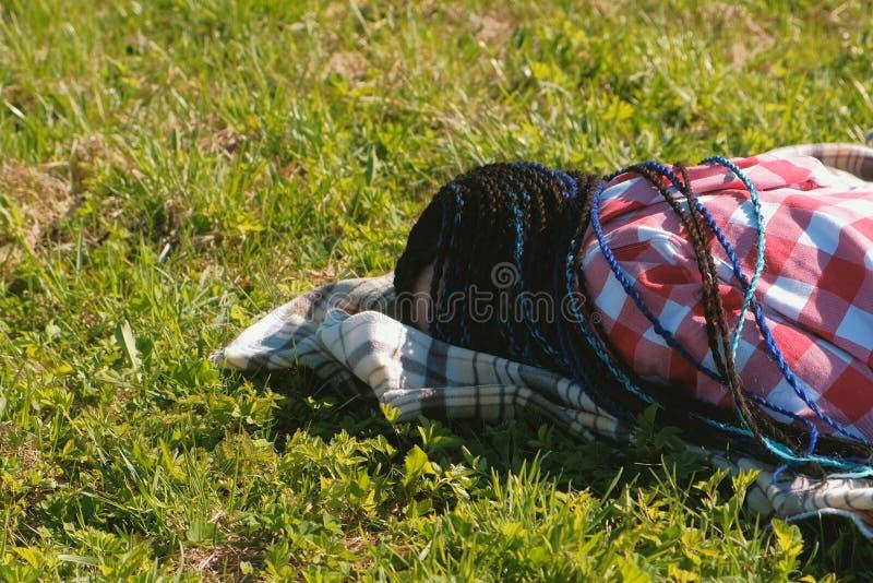 Onherkenbare vrouw met blauwe Afrikaanse vlechten die op het gazon in het Park slapen stock foto's