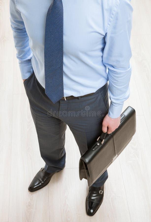 Onherkenbare zakenman die een zwarte aktentas houden stock fotografie