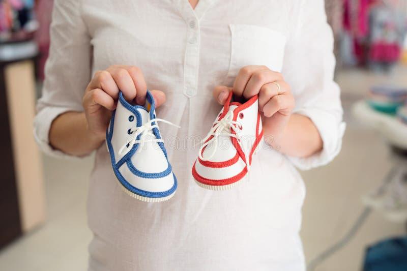 Onherkenbare zwangere vrouw het winkelen schoenen voor haar baby stock foto's