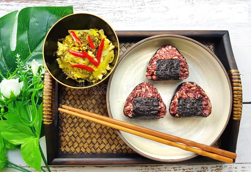 Onigiri , brown rice , with fried preservative vegetable put on royalty free stock photography