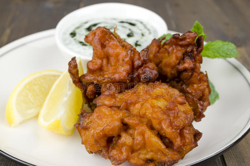 Onion Bhajis & Mint Raita. Deep fried south asian snack yoghurt and mint dip, garnished with mint leaves and lemon wedges on a white plate royalty free stock image