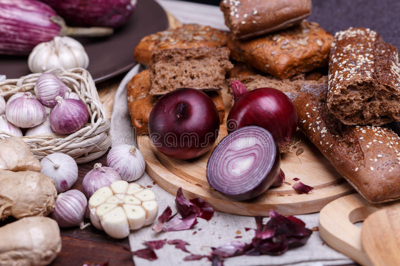 Onion, bread and garlic. On a wooden cutting board stock photos