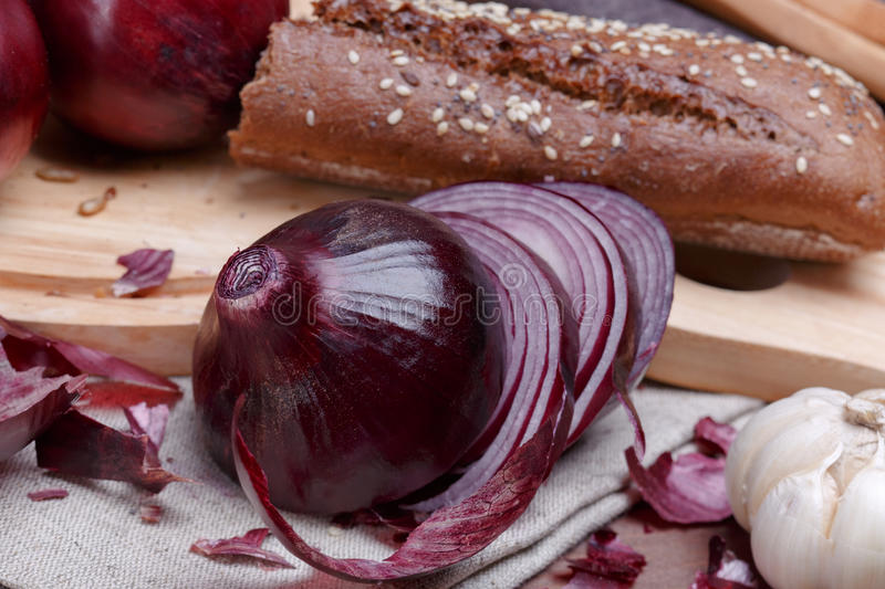 Onion, bread and garlic. On a wooden cutting board stock images