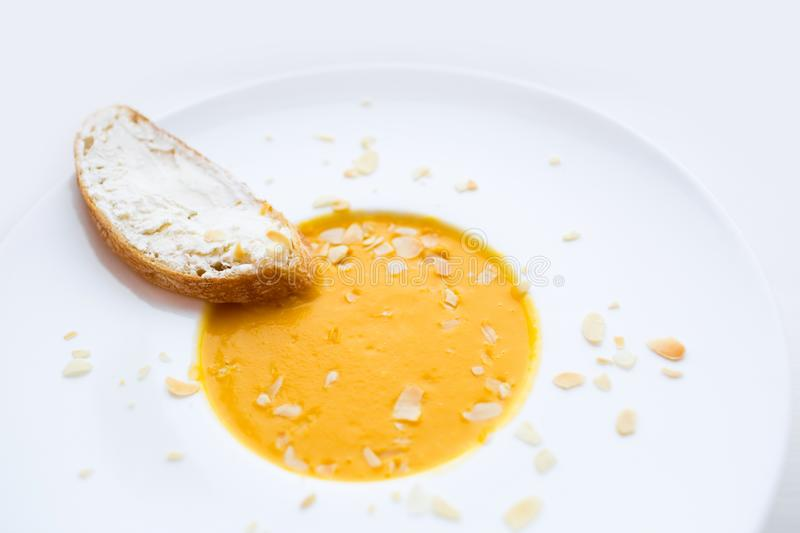 Onion cream soup with toast. Vegetable cream soup with pumpkin in a white bowl and a slice of bread with cheese. Healthy food. Hea stock images