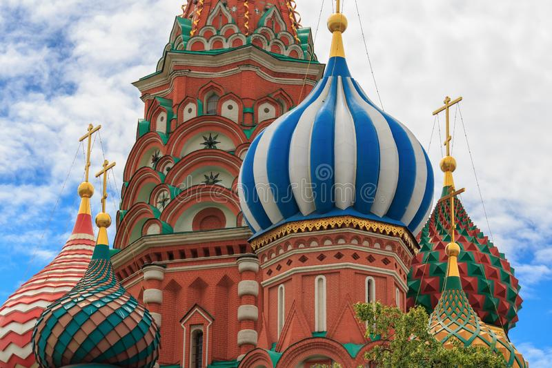 Onion domes of St. Basil`s Cathedral on Red square in Moscow closeup against blue sky with white clouds royalty free stock photography