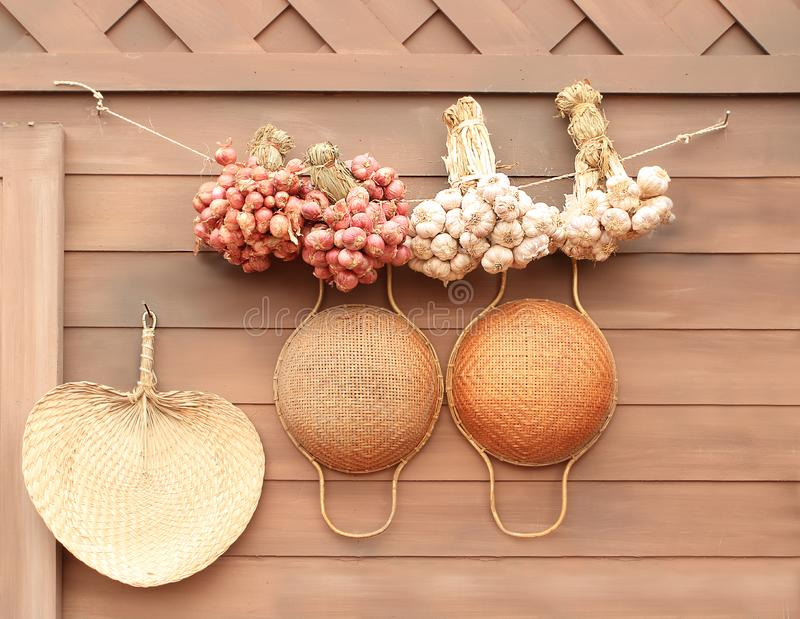Onion and garlic hung on the wall background in kitchen thailand style stock photo