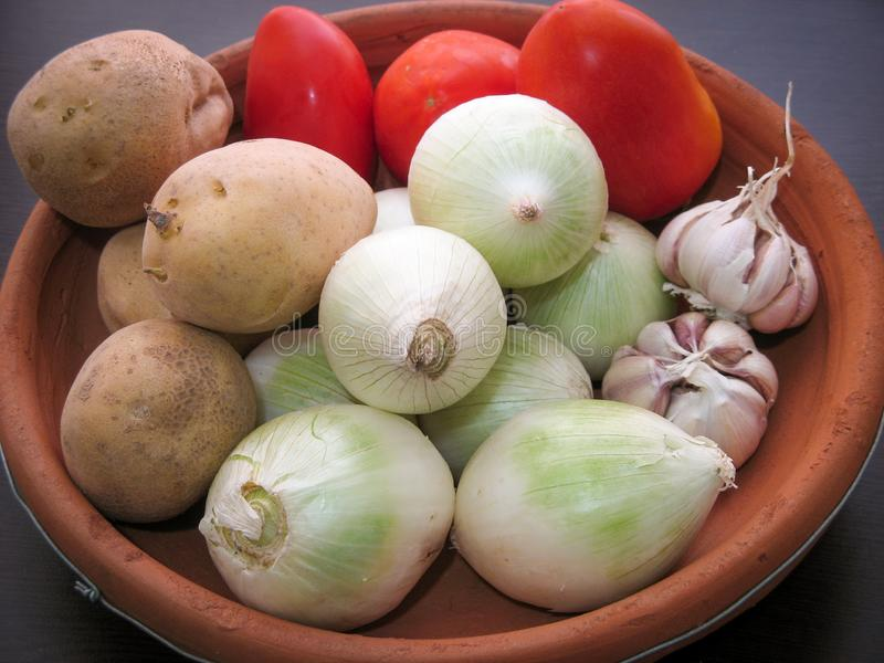 Onion Garlic Potato Tomato Vegetables. Closeup of fresh organic vegetables in a clay dish royalty free stock photography