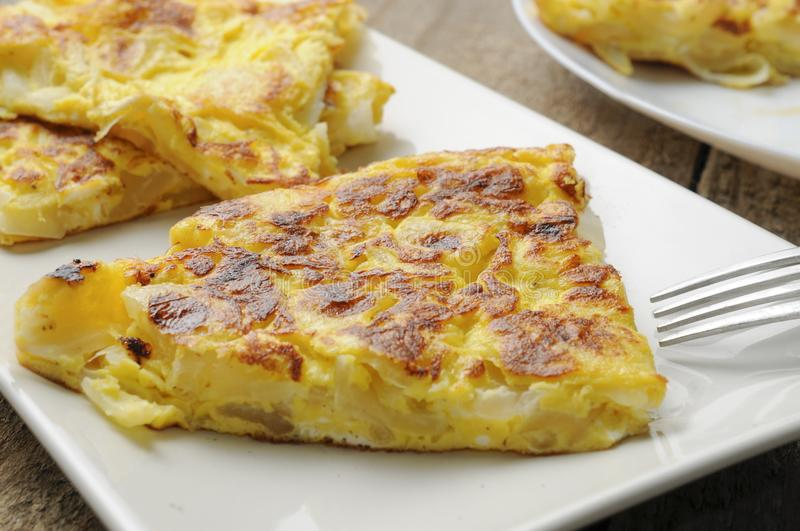Onion omelette divided in slices on white plate on wooden table royalty free stock photo