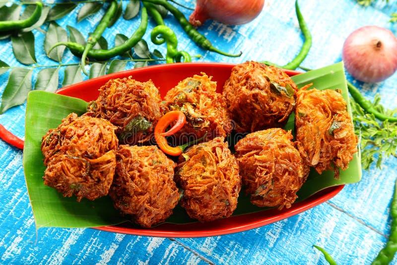 Onion pakora fritters. Indian street snack onion pakoda or fritters royalty free stock photo