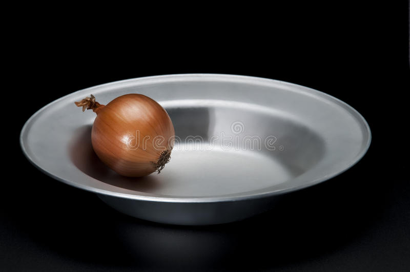 Onion on the plate on black royalty free stock photography