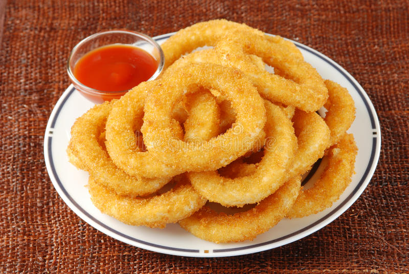Onion rings. Golden onion rings and ketchup royalty free stock images