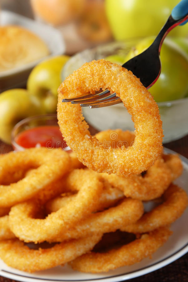 Onion rings. Golden onion rings and ketchup royalty free stock photography