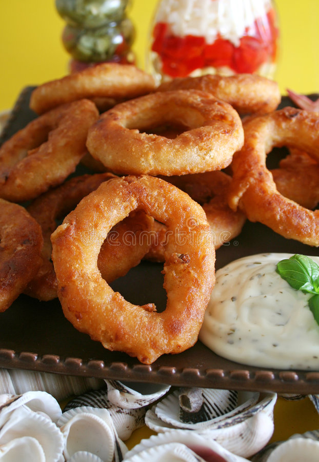 Onion rings. Some fresh onion rings with some sauce royalty free stock images
