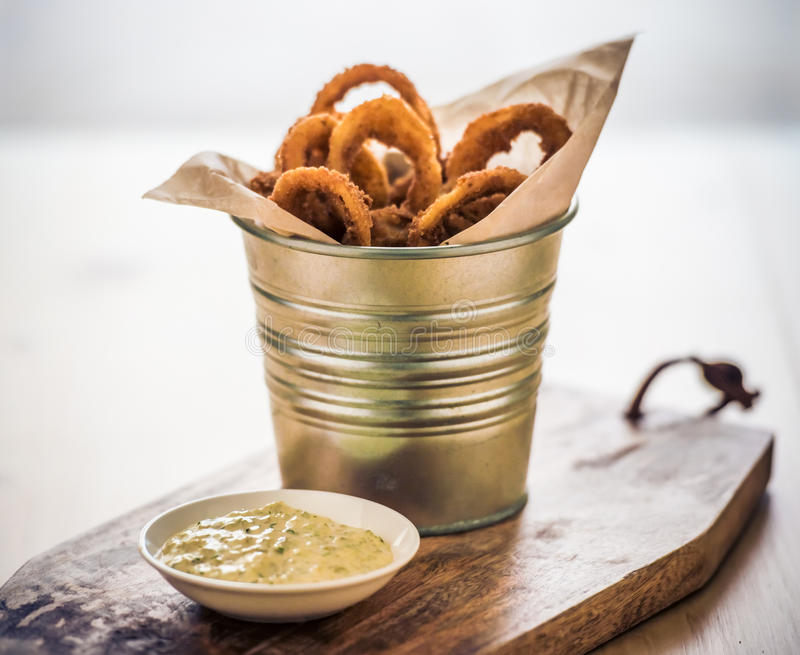 Onion rings. Deep fried onion rings with garlic sauce on wooden board royalty free stock image