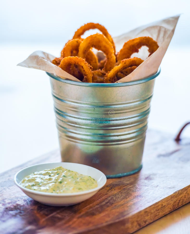 Onion rings. Deep fried onion rings with garlic sauce on wooden board stock image
