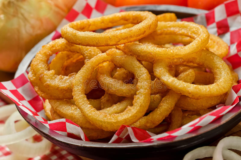 Onion Rings. A serving of delicious breaded and deep fried golden brown onion rings royalty free stock photos