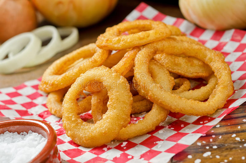 Onion Rings. A serving of delicious breaded and deep fried golden brown onion rings royalty free stock photo