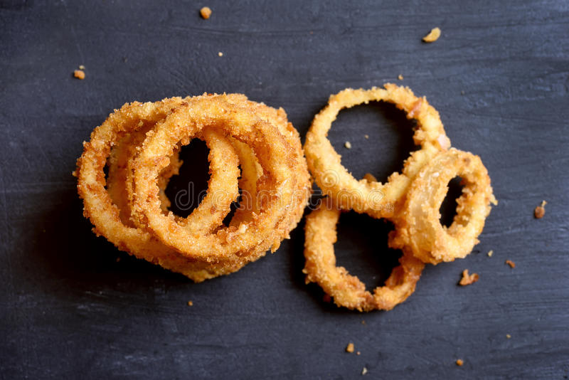 Onion rings, top view. Onion rings on dark stone background, close up, top view royalty free stock images