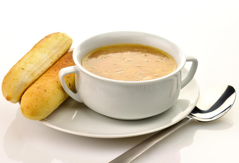 Onion soup. French Onion Soup in a white bowl with bread sticks stock photo