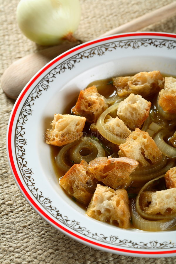 Onion soup. With bits of bread in the plate stock images