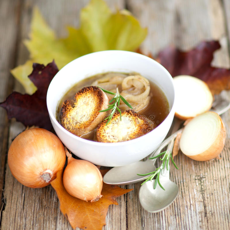 Onion soup. With baguette and rustic decoration stock images