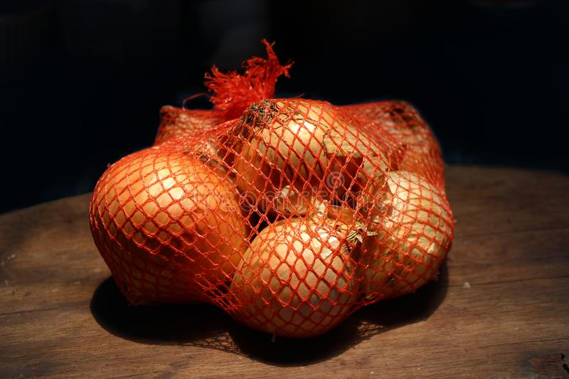 Onions in bags on wooden royalty free stock image