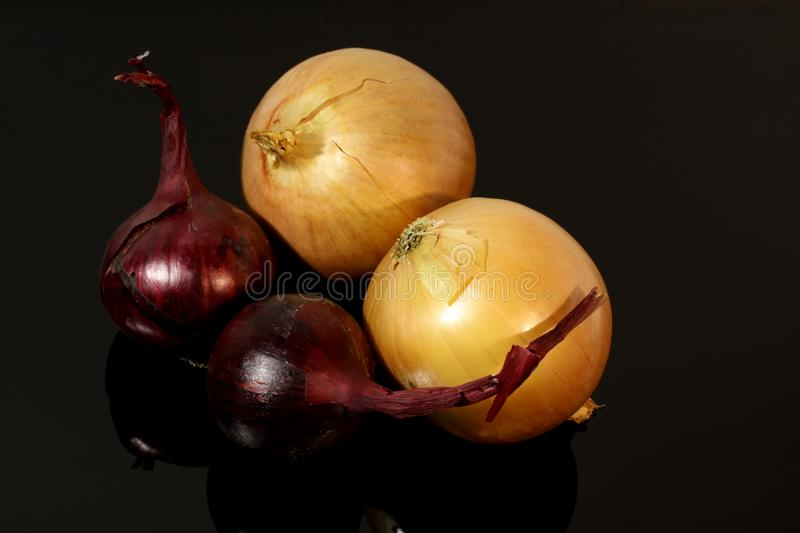 Onions and blue onions on a mirrored table stock image