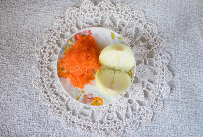Onions and carrots on a plate standing on a knitted napkin royalty free stock photography